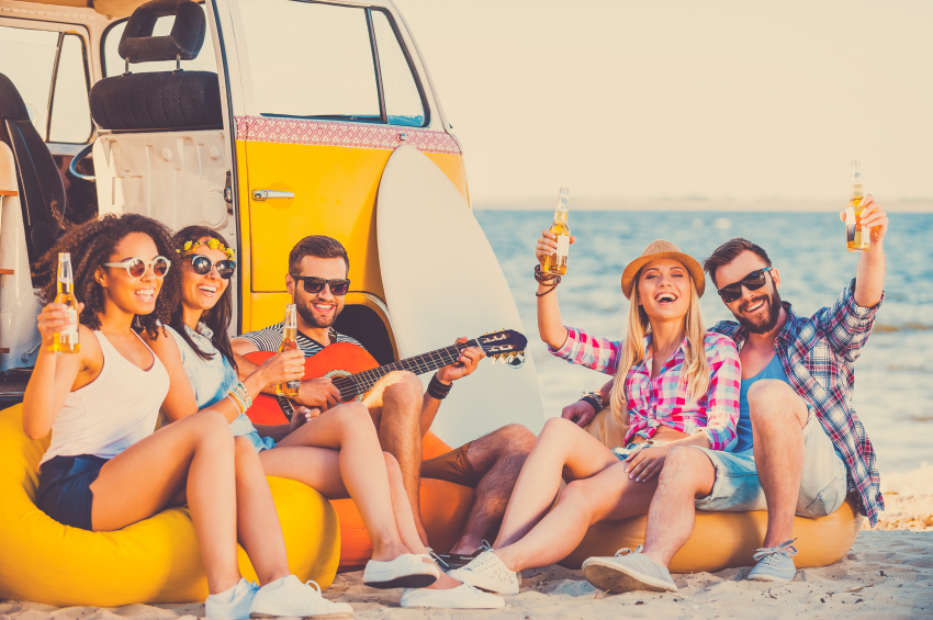 Enjoying summer time together. Group of happy young people having fun together while sitting on the beach near their retro van