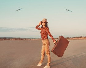 Happy woman traveler with suitcase walking on road, airplanes in sky