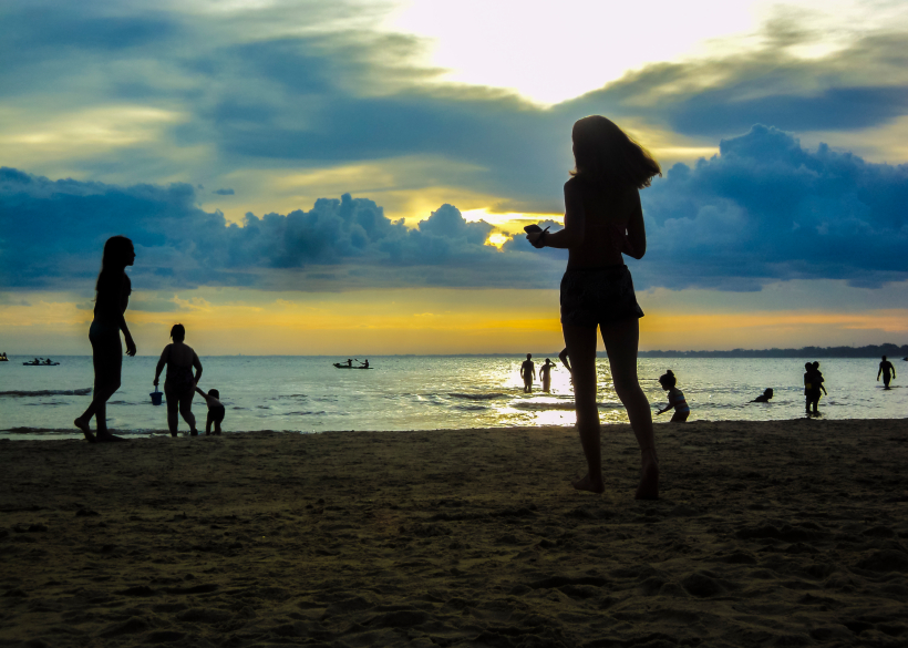 CANELONES, URUGUAY, FEBRAURY - 2015 - Group of people silhouettes at the beach with the sunset at the background