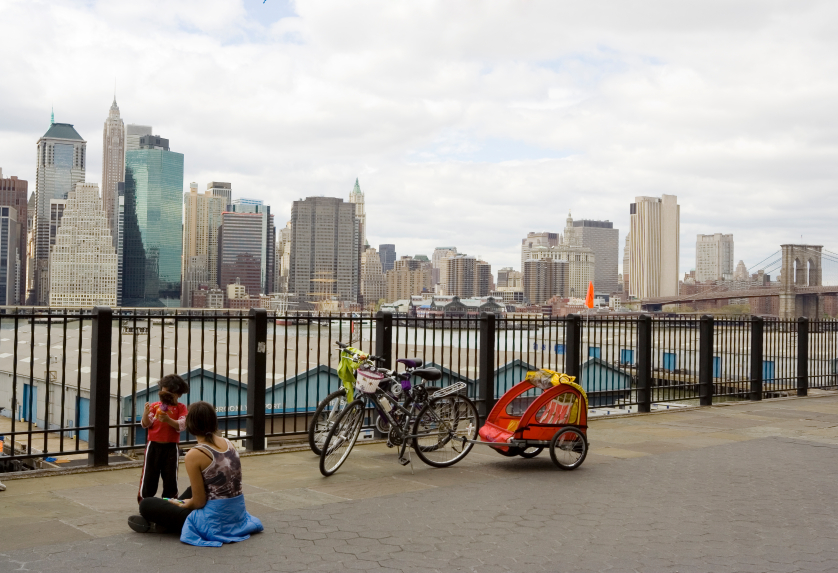 mother and daughter resting after biking with Manhattan skyline on background