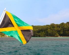 Jamaica flag waving sea beach sky. Selective focus on flag
