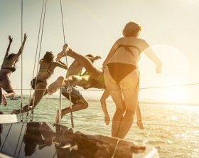 group of friends jumping in the water from the boat during an excursion. concept about vacations,leisure and fun