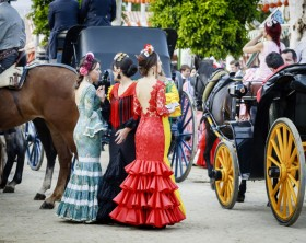 """Seville, Spain - April 28, 2015: Young women wearing traditional flamenco dress at the April Fair Seville . The Seville Fair """"Feria de abril de Sevilla"""" is one of most important celebration of the city, it begins one or two week after easter Holy Week, and is a big party where you can see women with traditional flamenco dress, beautiful horses, traditional carriages, dance Sevillanas, eat great tapas and drink liquors of the area"""