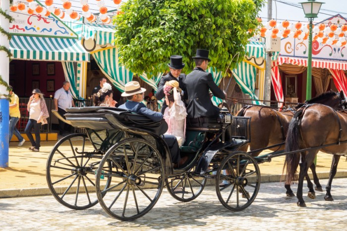 """Seville, Spain - April 23, 2015: People in traditional dress travelling in a horse drawn carriage at the Seville Fair. The Seville Fair """"Feria de abril de Sevilla"""" is one of most important celebration of the city, it begins one or two week after easter Holy Week, and is a big party where you can see women with traditional flamenco dress, beautiful horses, traditional carriages, dance Sevillanas, eat great tapas and drink liquors of the area"""