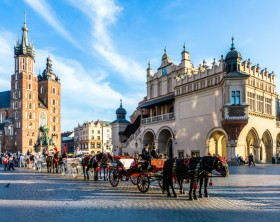 KRAKOW, POLAND - OCT 7, 2014: Horse carriages in front of Mariacki church on main square of Krakow city. Taking a horse ride in a carriage is very popular among tourists visiting Krakow