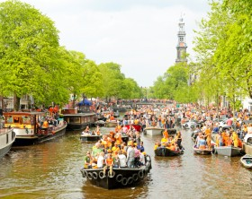 AMSTERDAM - APRIL 26: Amsterdam canals full of boats and people in orange at the Prinsengracht during the celebration of kings day on April 26, 2014 in Amsterdam, The Netherlands