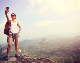 woman hiker taking photo with smart phone at mountain peak