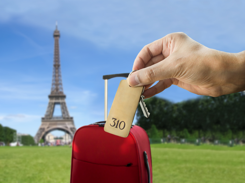 guest holding the hotel room key at Paris with Eiffel Tower in the background