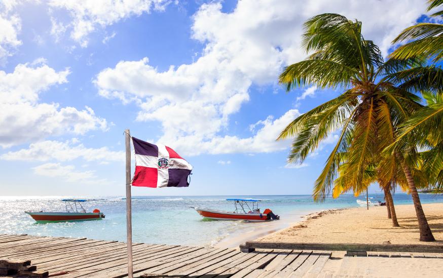 Caribbean beach and Dominican Republic flag on Saona island