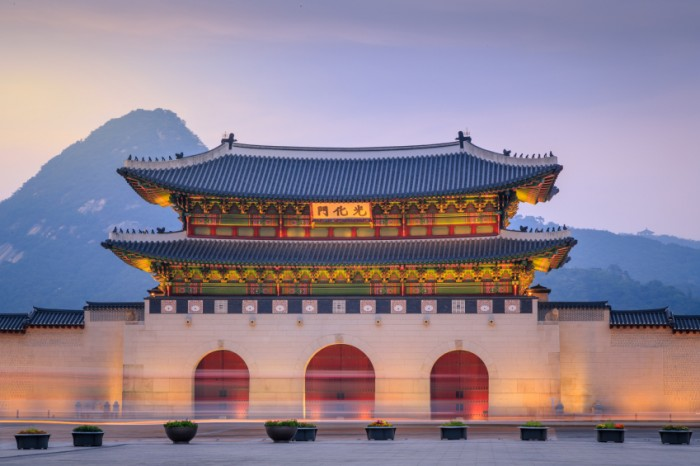 Gyeongbokgung Palace At Twilight Sunset In South Korea, with the name of the palace 'Gyeongbokgung' on a sign