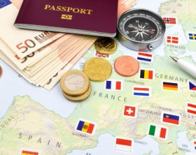 An arrangement of Euro notes, coins, passport and compass on slate.