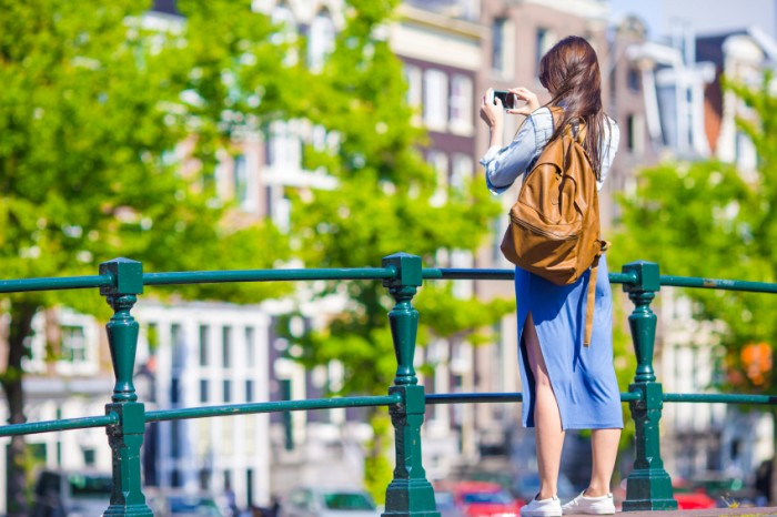 Tourist woman taking photo with cell phone