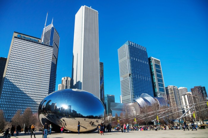 ?hicago, USA - April 9, 2014: Cloud Gate sculpture with tourists in Millenium park in Chicago, IL. This public sculpture is the centerpiece of the AT&T Plaza in Millennium Park within the Loop community area.