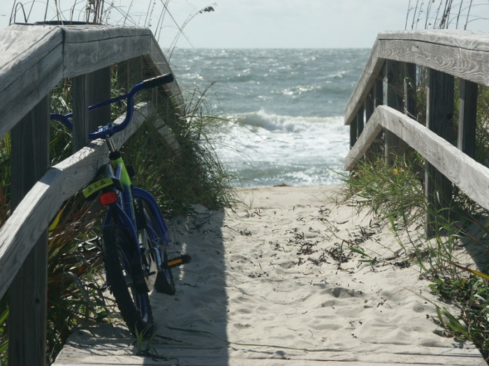 Bicycle resting on boardwalk beach dune walkover at St. George Island, Florida with Gulf of Mexico surf in background.