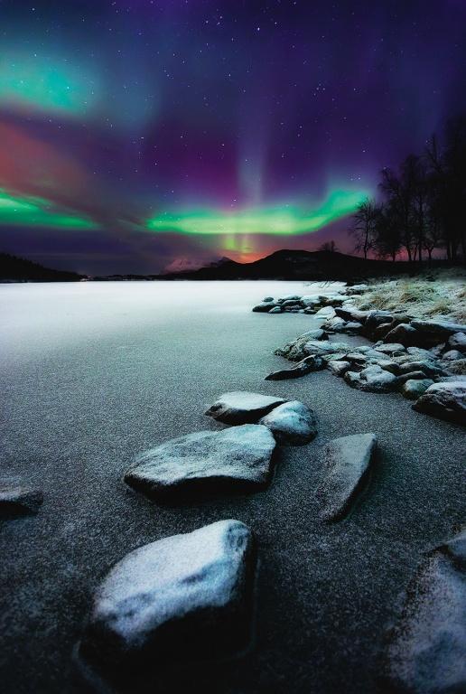 Milhares de turistas chegam a Noruega ávidos por ver o céu repleto de cores brilhantes.