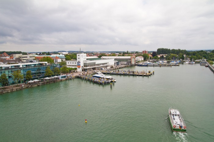 """""""Friedrichshafen, Germany - July, 2th 2012: Overlooking of the harbor of Friedrichshafen and the blimp museum. Friedrichshafen is located on the shores of Lake Constance, Baden-Warttemberg, in the border triangle of Germany, Austria and Switzerland. The city is not only as a tourist destination but also as a city of the Zeppelins known. Today there are companies in Friedrichshafen aviation and aerospace, automotive and high technology."""""""
