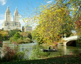 New York, USA - October 26, 2013: People renting a rowboat and enjoying beautiful day in Central Park at New York City.  The San Remo Building is at the background.