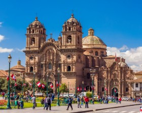 Cuzco, Peru - July 16, 2013: tourists at the Plaza de Armas and Society of Jesus church