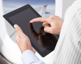 Businessman holding digital tablet at airplane