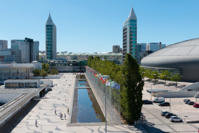 Lisbon, Portugal - August 07, 2014: Visitors comming in and out of the Vasco da Gama Shopping, Sao Rafael Tower in the back and Homem-Sol (Sun-Man) Sculpture. Parque das Nacoes.