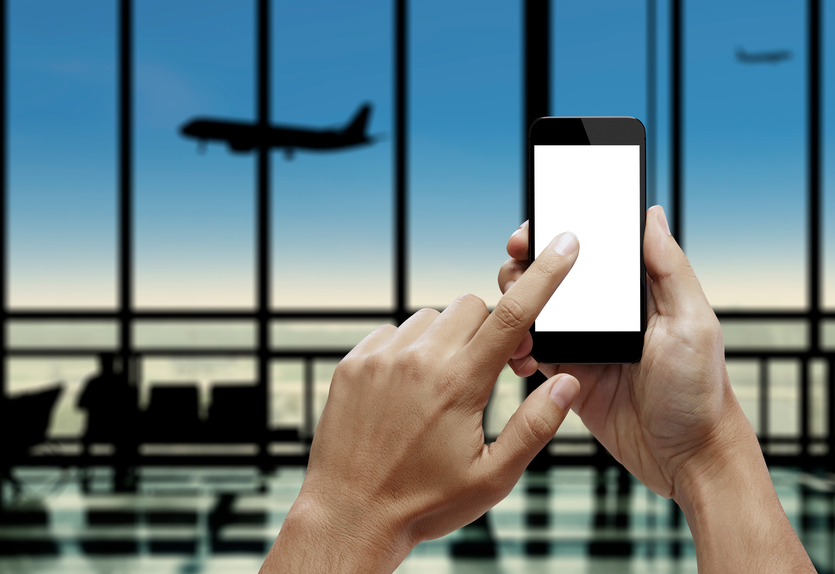 Hand holding smartphone with forefinger touching the screen and airport background.