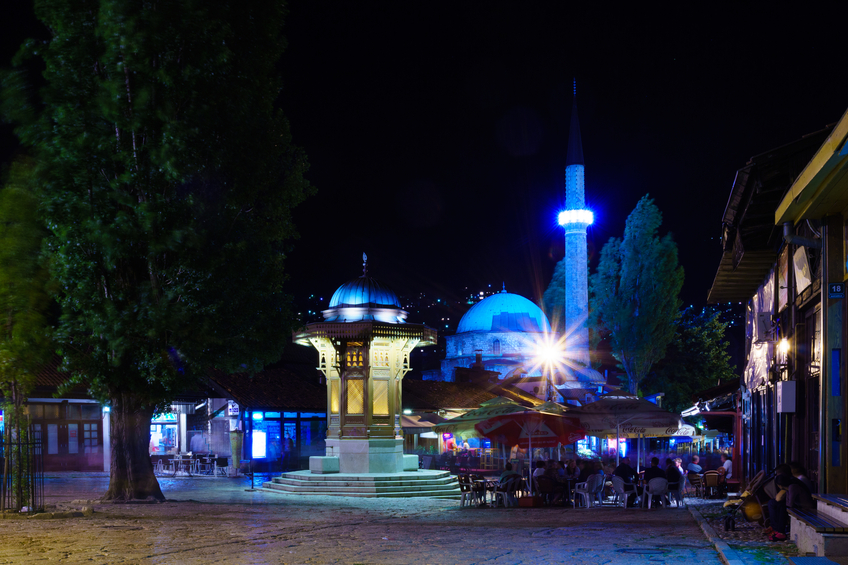 Sarajevo, Bosnia and Herzegovina - July 4, 2015: Night scene, with the Sebilj fountain, Havadze Duraka Mosque, local businesses, locals and tourists, in Sarajevo, Bosnia and Herzegovina