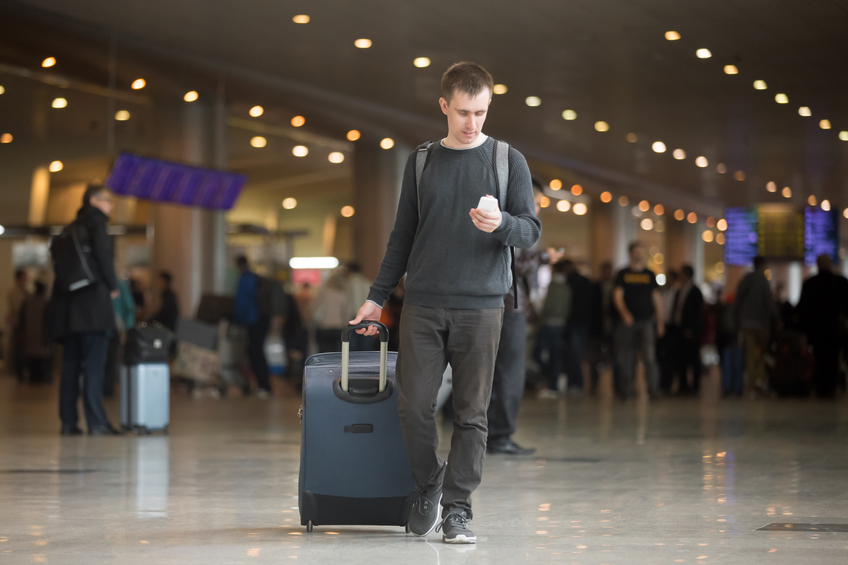 Young smiling handsome man in 20s walking in modern airport terminal, using smart phone app in public wifi area, texting, travelling with luggage bag, wearing casual style clothes
