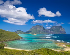 View south over the stunning turquoise lagoon to the peaks of Mts Lidgbird and Gower. Taken from Mt Eliza on Lord Howe Island, Australia. Fluffy clouds stand out from the deep blue sky overhead. This tiny island is a delightful tourist destination.
