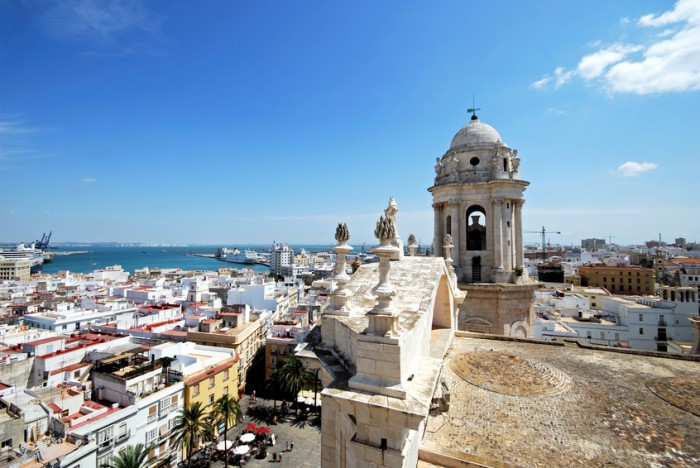 Cadiz, Spain - September 8, 2008: Eastern bell tower and rooftop statues on the Cathedral with views towards the port and tourists in the square, Cadiz, Cadiz Province, Andalusia, Spain, Western Europe.