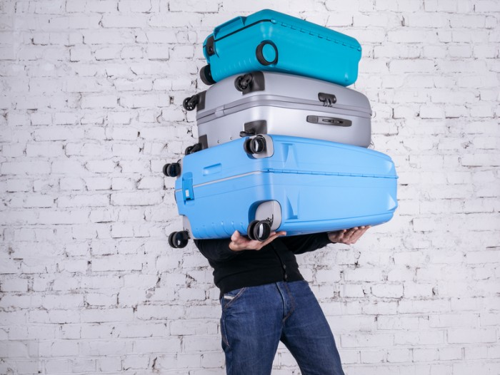 Man holding three heavy suitcases in hand. Travel light.