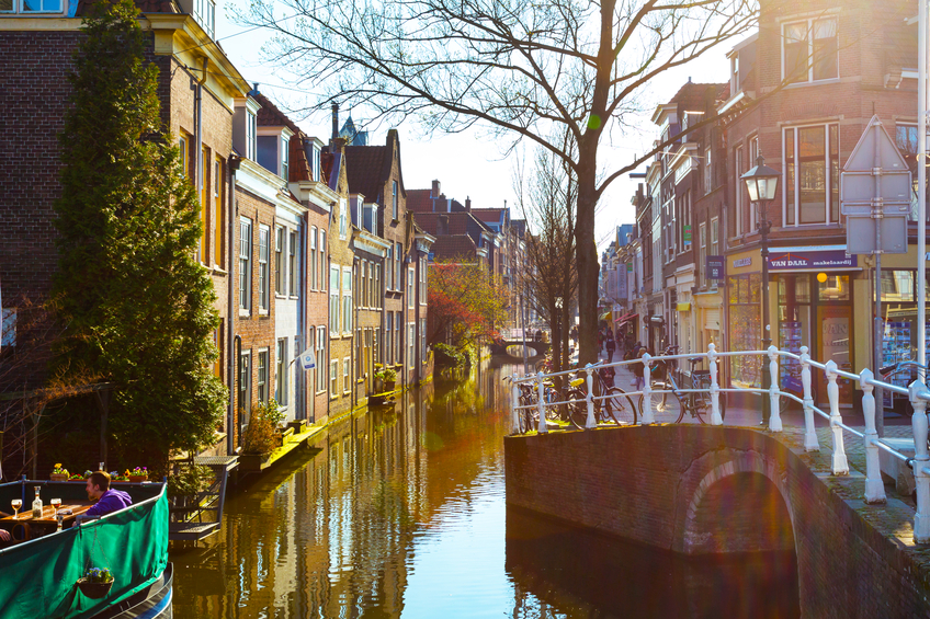 Delft, Netherlands - April 8, 2016: Sunset street view with traditional dutch houses, bicycles, canal in downtown of popular Holland destination