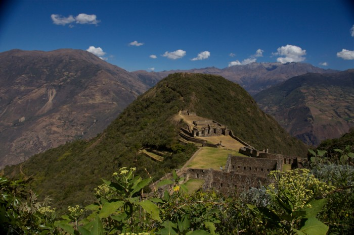Choquequirao asurrounded by lush mountains, Aerial view, blue sky with some clouds.