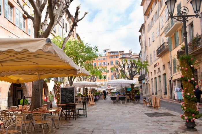 Grasse, France - May 8, 2013: Early in the morning just opened cafes on the town square (Place aux Aires), and tourists walking and looking for suitable one.