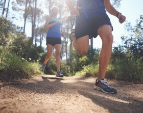 Fit marathon couple trail running together for sport and healthy living