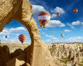 Hand carved arch in limestone rock in Goreme National Park, Cappadocia. Colorful hot air balloons flies in blue sky in Kapadokya, Turkey