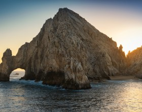 Sun setting over Land's End natural rock formation, El Arco, in Cabo San Lucas, Mexico