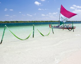 Jericoacoara, Brazil - November 22, 2011: Sailing boat and it's owner in a lagoon of Jericoacoara. The green hammocks for relaxation are popular and easy to find in every lagoons.