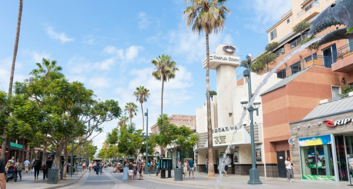 Santa Monica, USA - October 5, 2015: people and tourists wandering the 3rd St. Promenade street,shops Broadway Theater and water spurting from dragon head water feature Santa Monica Los Angeles USA
