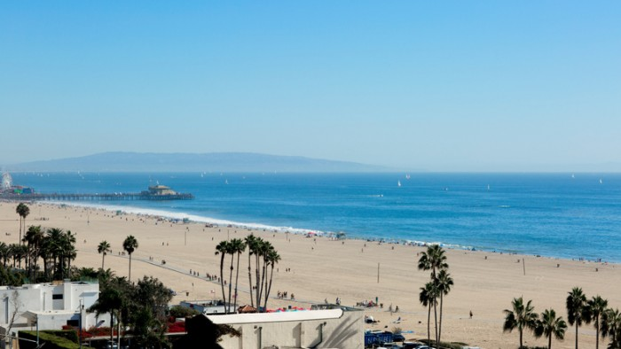 The beach is in the Santa Monica, California. The Pacific Ocean is in the Los Angeles on a Sunny day.
