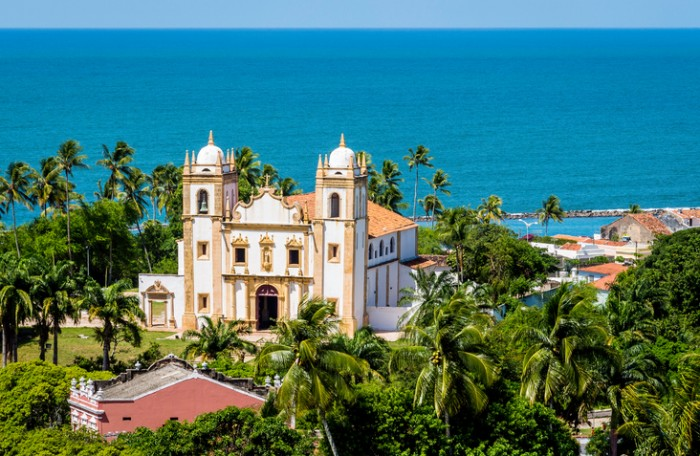 Aeril view of Olinda in Pernambuco, Brazil showcasing the Baroque architecture of Se Church by the Atlantic Ocean on a sunny summer day.