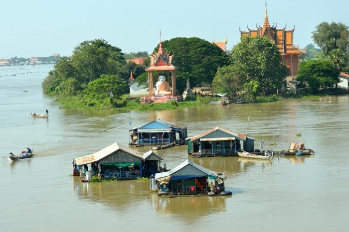 Phnom Penh, Cambodia. Oct 29, 2013. Cambodians ferry their small boats to and from their floating homes in the Mekong River.