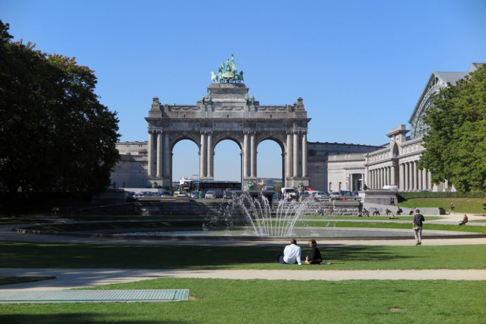 Brussels, Belgium - October 2, 2015:  A couple sits before the fountain and arch in the Parc du Cinquantenaire.  The park and arch, which wasn't completed until 1905, were built to celebrate the Golden Jubilee of Belgian independence in 1880.