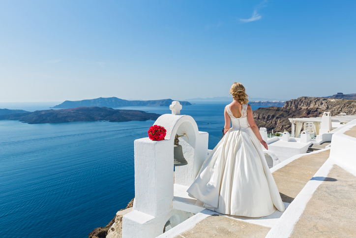 Bride with a bouquet of flowers, look at the sea