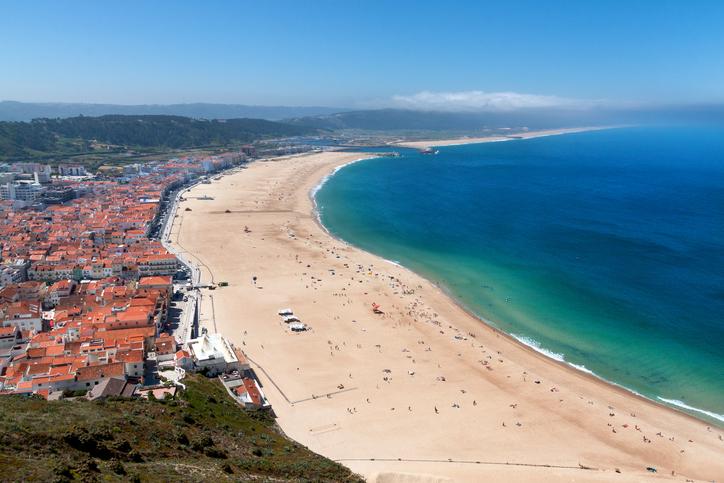 View over the sandy beach coastline with sunlight, ocean, blue sky, sandy beach at Nazare, Portugal