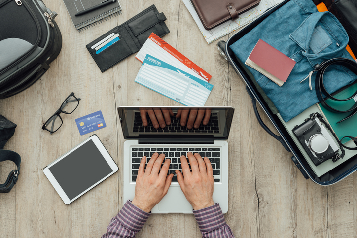 Traveler getting ready for a trip, he is packing his bag and planning a journey online using a laptop, flat lay