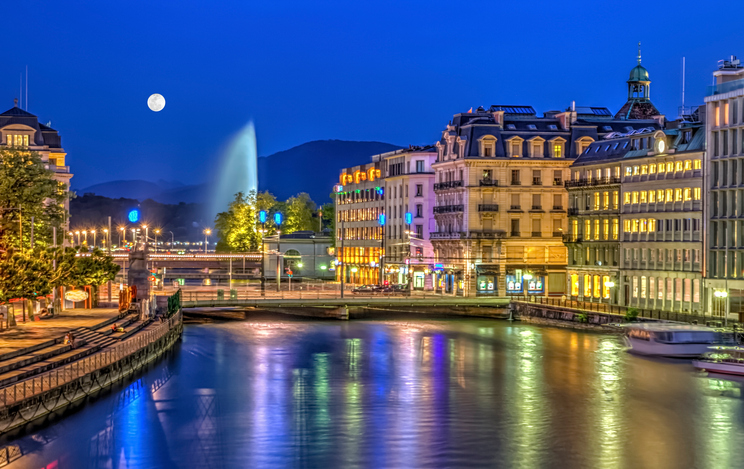 Urban view with famous fountain by night with full moon, Geneva, Switzerland, HDR