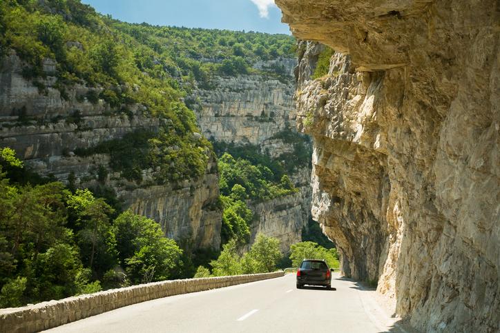 Black colour hatchback car on background of French mountain nature landscape.