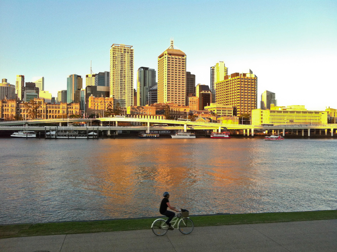 Brisbane, Australia - March 14, 2015: A man ride a bicycle on Brisbane River Southbank parkland. The sunlight shines on high rise buildings on Northbank. This photo is taken in the afternoon.