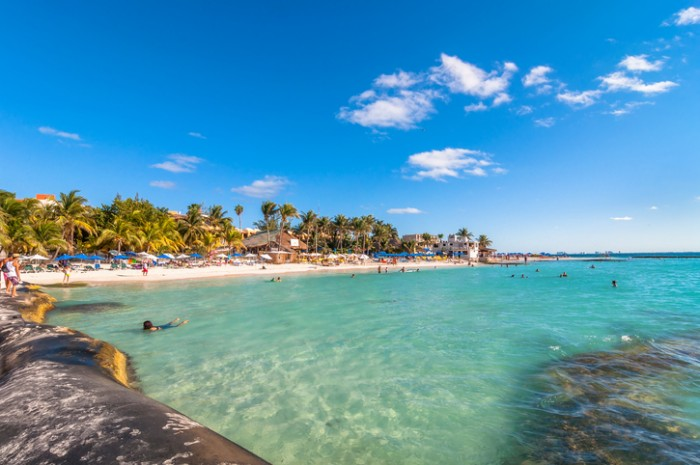 Isla Mujeres, Mexico - April 21, 2014: tourists enjoy tropical sea on famous Playa del Norte beach in Isla Mujeres, Mexico. The island is located 8 miles northeast of Canc?n in the Caribbean Sea.