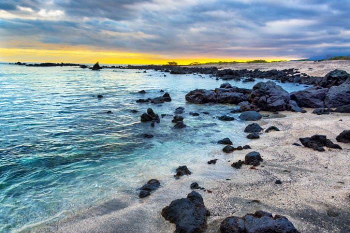 Sunset over a rocky beach on Isabela Island in the Galapagos Islands in Ecuador